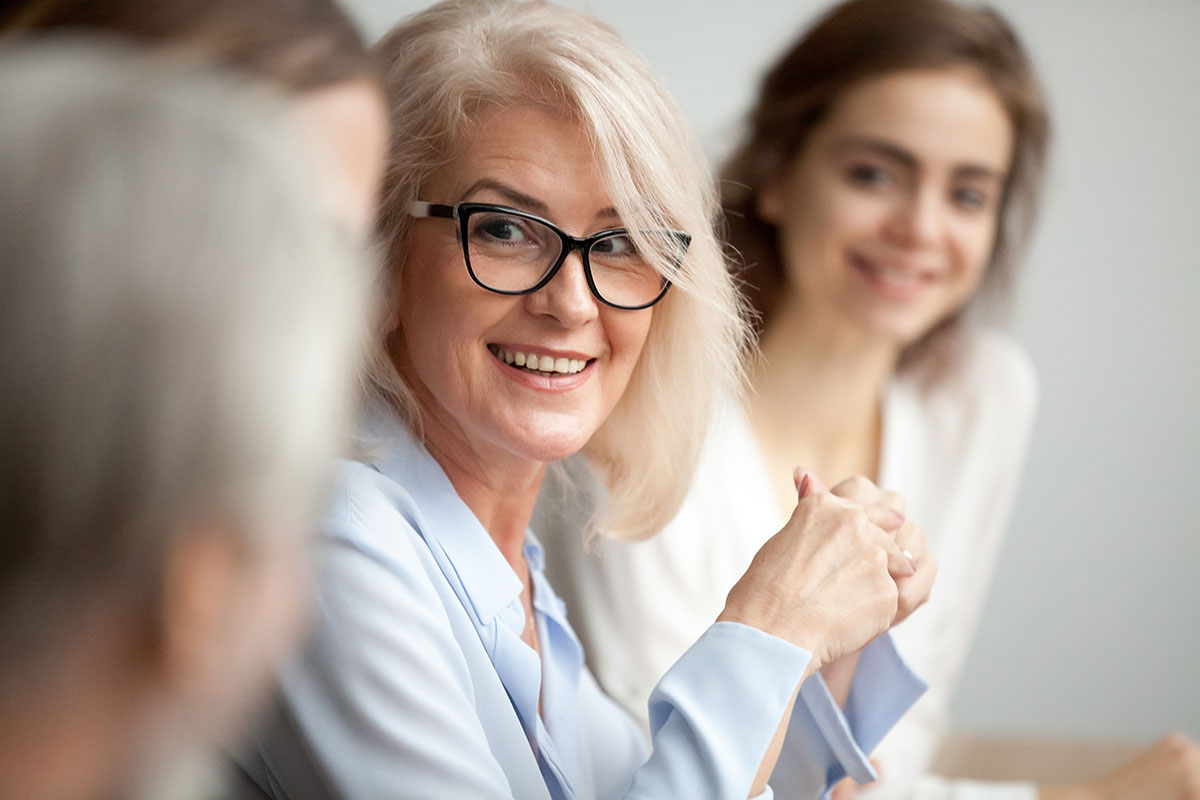 older woman in professional clothing smiling in a retirement plan meeting