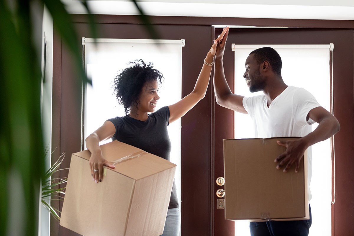 young couple high-fiving as they move into their new home