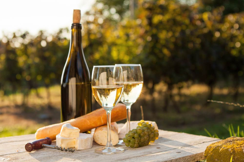 bottle of white wine with two glasses and food assortment