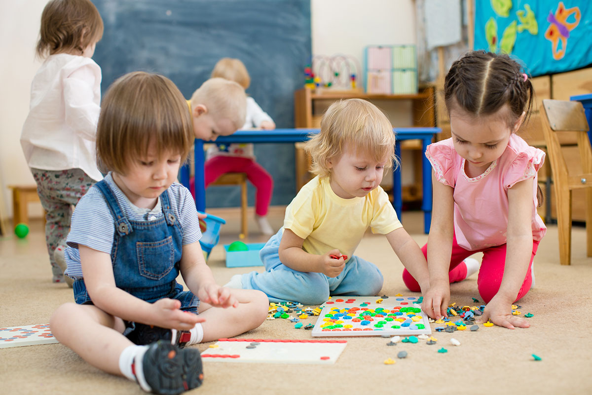 three toddlers playing in a childcare facility