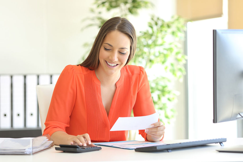 young woman in a bright orange blouse looking over tax deductions