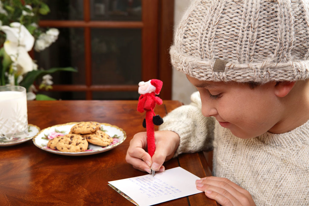 young boy making a holiday wishlist