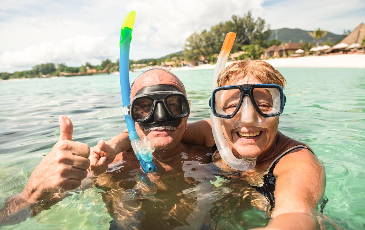 Senior couple snorkels together smiling